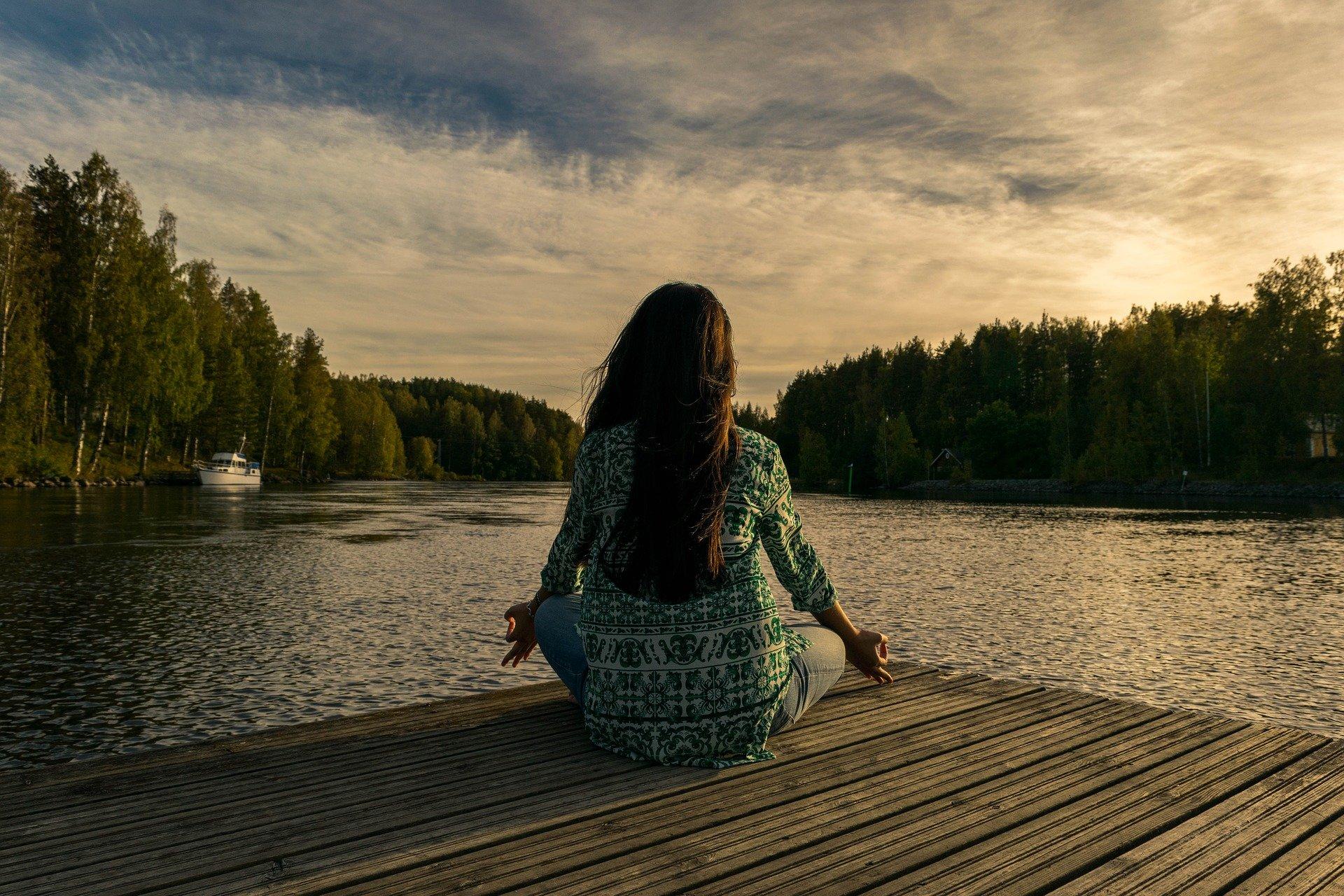 Dame dyrker yoga i naturen